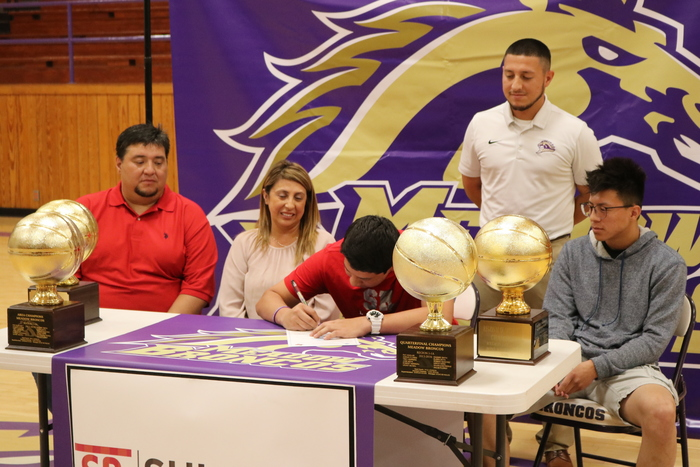 Jacob Flores signing with family present.